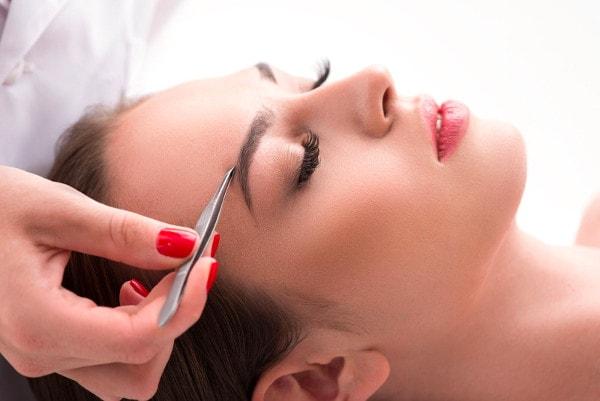Une esthéticienne épile les sourcils de sa cliente qui est allongée à l'aide d'une pince à épiler