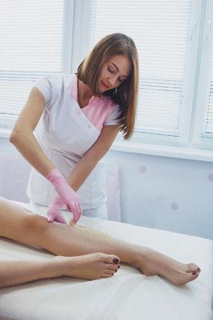 Une esthéticienne en blouse de travail épile la jambe d'une femme à la cire