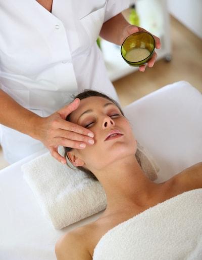 Femme allongée confortablement avec son esthéticienne appliquant une crème de soin du visage