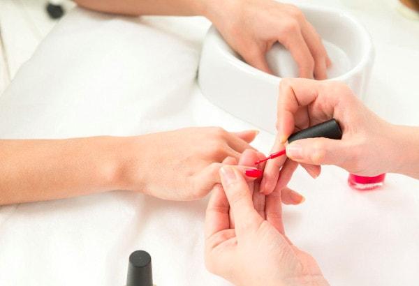Une esthéticienne réalise une manucure à une cliente en lui appliquant du vernis à ongles rouge