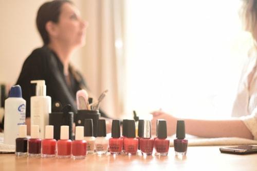 Une esthéticienne à domicile s'apprête à appliquer du vernis à ongles à sa cliente, elle a le choix entre plusieurs couleurs de vernis.