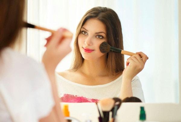 Une jeune femme souriante se maquille avec un pinceau devant son miroir