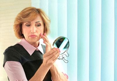 Une femme âgée regarde la peau de son visage dans un miroir