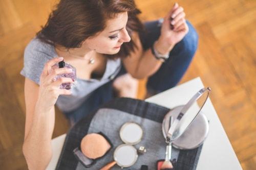 Une jeune femme se prépare chez elle : elle met du parfum et finalise son maquillage.