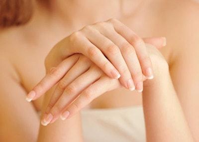 Les jolies mains d'une femme ornées d'une french manucure
