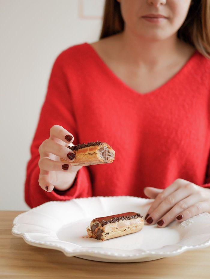 Une jeune femmes aux ongles manucurés et vernis tient dans sa main une pâtisserie