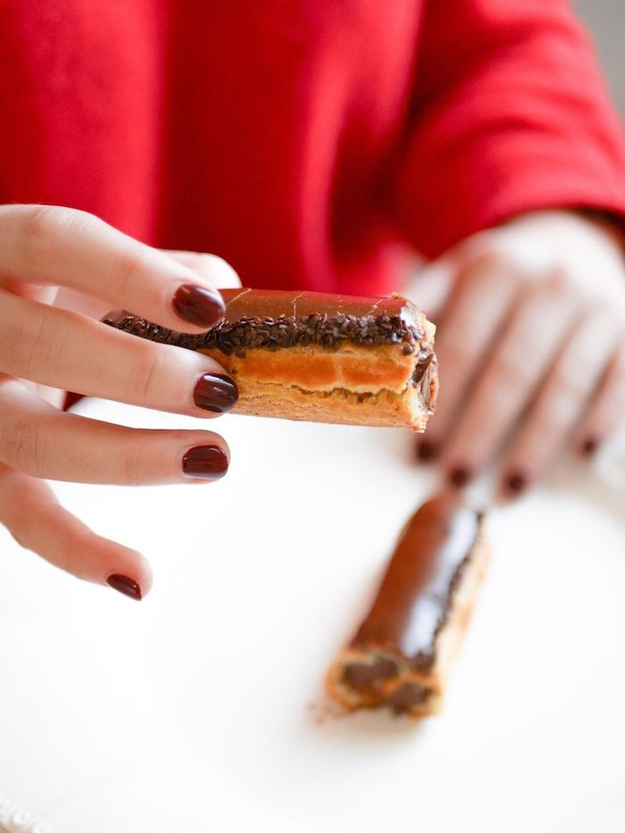 Une jeune femme aux ongles vernis bordeaux tient dans ses mains un éclair au chocolat