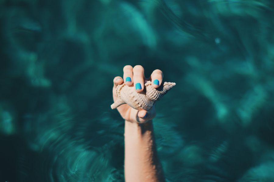 Une main aux ongles bleus tient un coquillage au-dessus d'une eau turquoise