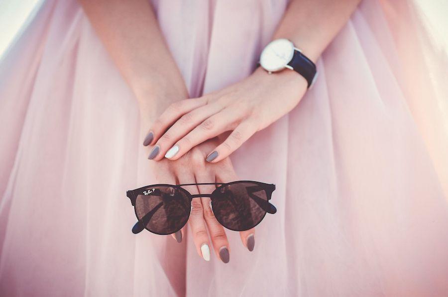 Une jeune femme en jupe tutu tient une paire de lunettes de soleil avec des ongles vernis mauve et blanc