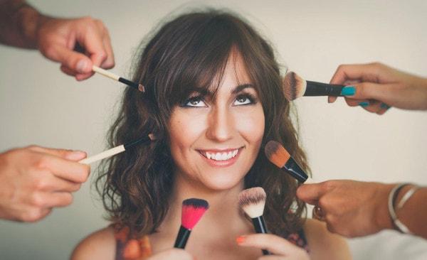 Une jeune femme maquillée et souriante avec des pinceaux de maquillage autour de son visage