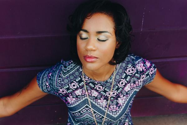 Une jeune femme adossée contre un mur profite du soleil, elle ferme les yeux et révèle un maquillage de jour élégant et lumineux.