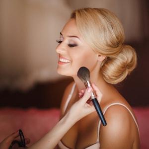 Une jolie mariée blonde se fait maquiller à domicile