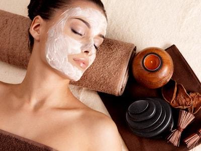 Jeune femme allongée dans un spa et recevant un soin du visage hydratant