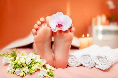 Pieds d'une personne allongée qui se relaxe avec autour d'elle des fleurs et des bougies