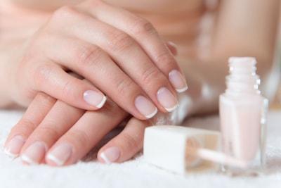 Les mains d'une femme avec les ongles embellis d'une french manucure avec un flacon de vernis