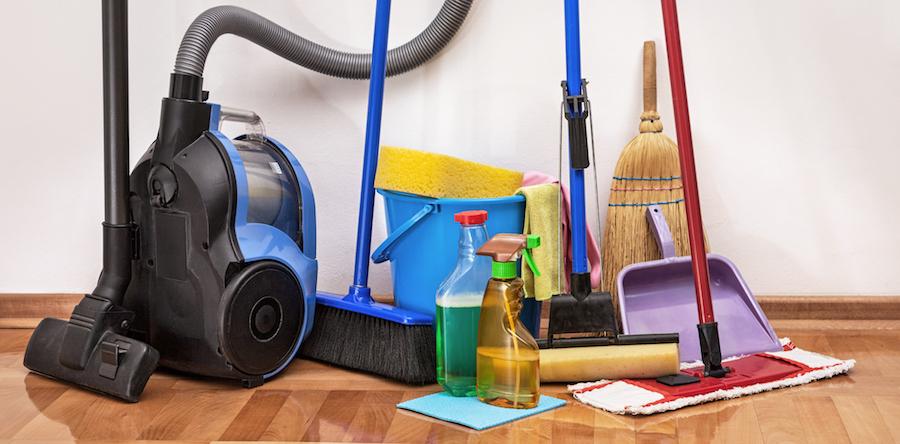 Un aspirateur, un balais et un ensemble de produits et ustensiles pour faire le ménage