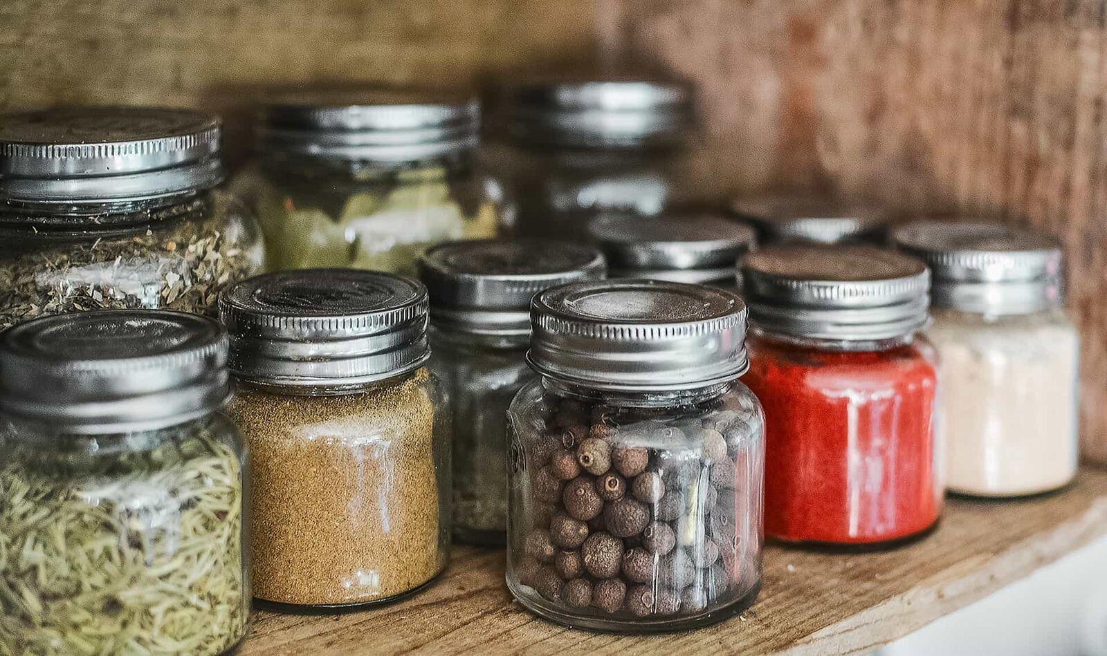 Bocaux d'épices sur une étagère en bois