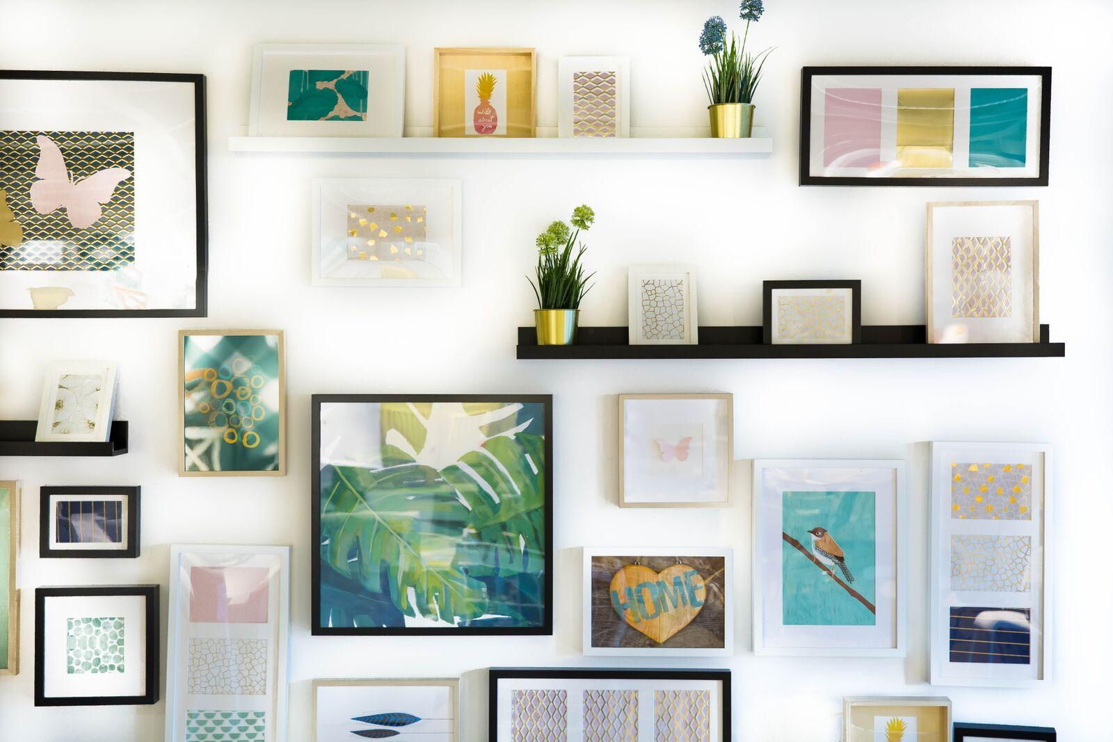 Un mur est recouvert de cadres de toutes les tailles avec des illustrations variées.