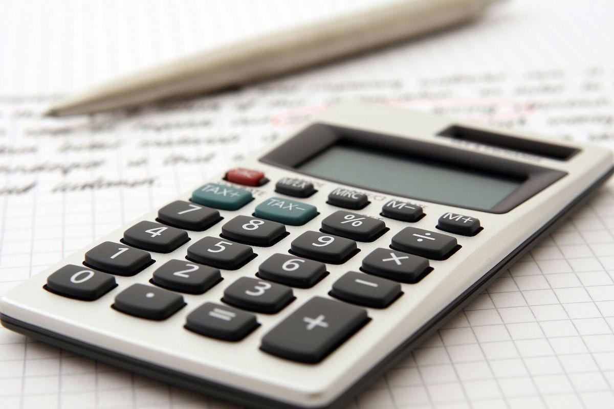 Gros plans sur une calculette et des notes de suivi administratif.