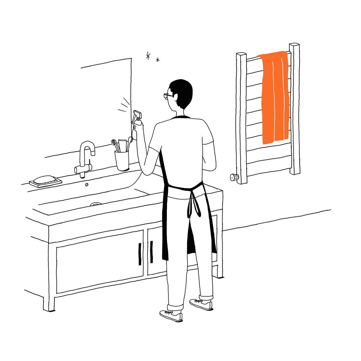 Un homme asperge le miroir d'une salle de bain avec un produit nettoyant.