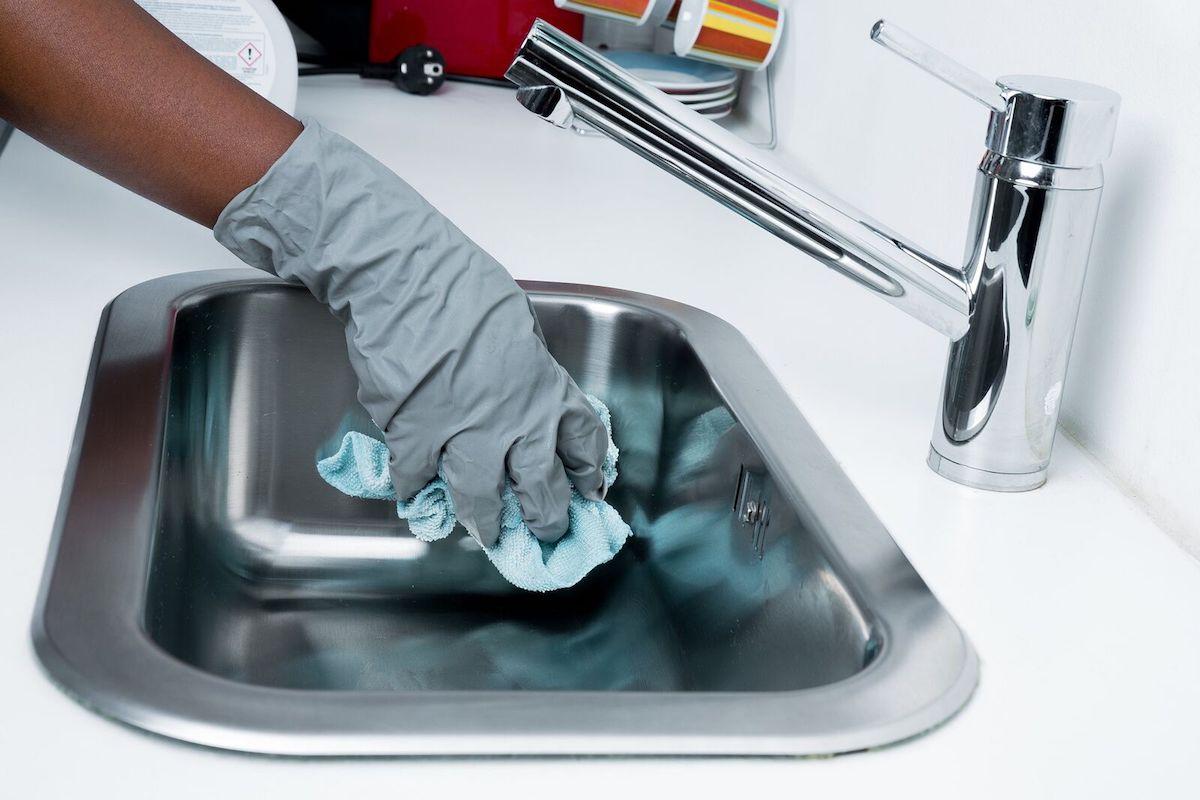 Gros plan sur une main avec un gant de ménage qui tient un chiffon pour nettoyer un évier.