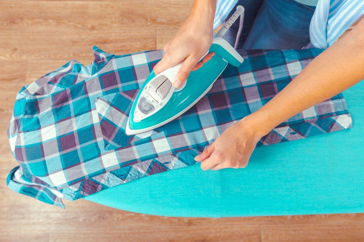 Une aide-ménagère repasse une chemise à carreaux.