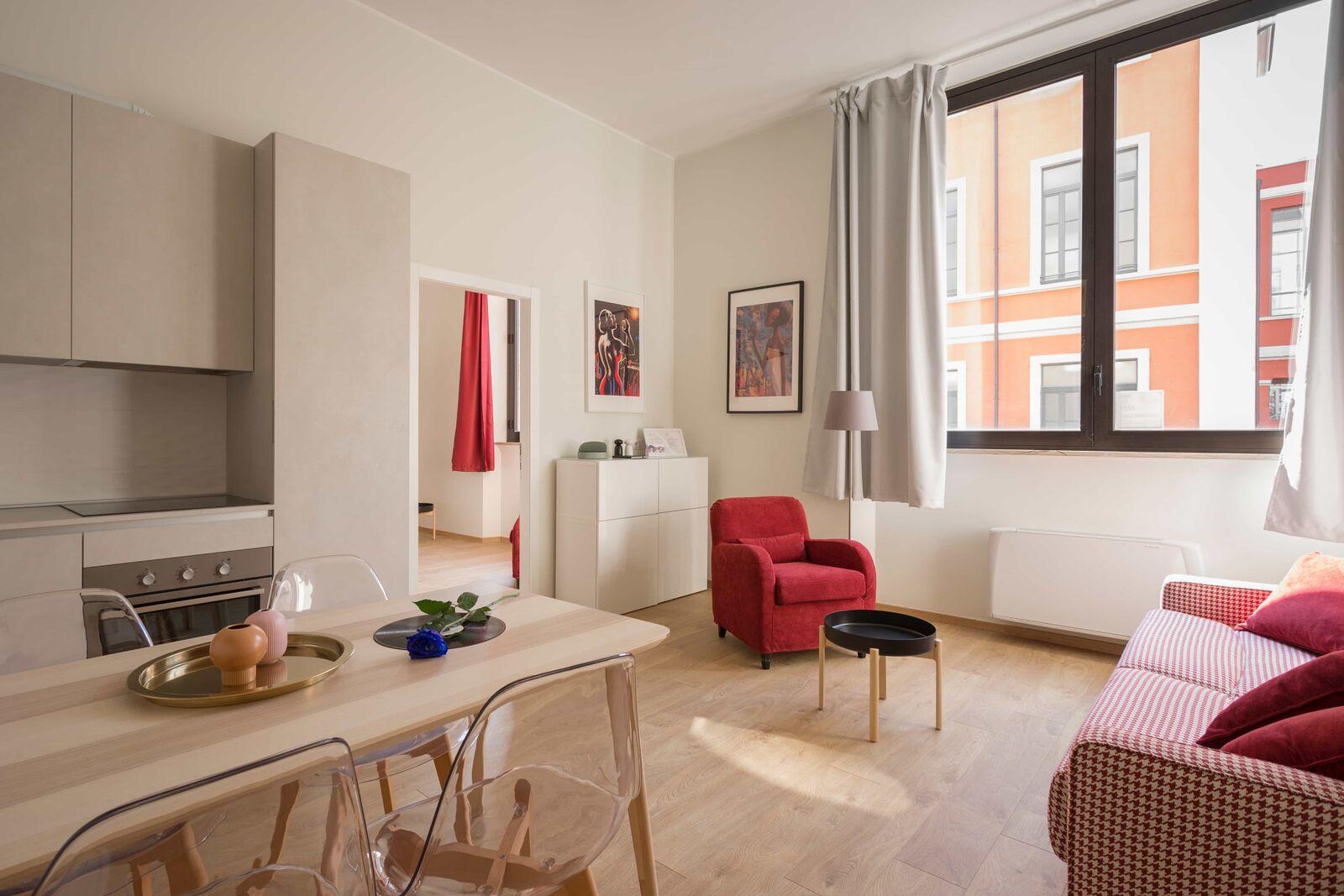 Salon et cuisine ouverte avec table en bois, canapé à carreaux rouges et fauteuil rouge