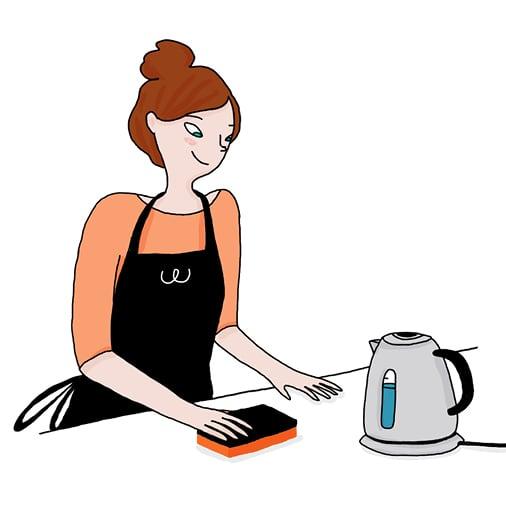 Une femme nettoie le plan de travail d'une cuisine avec une éponge