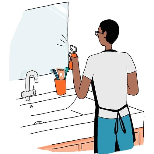 Un homme nettoie le miroir d'une salle de bain