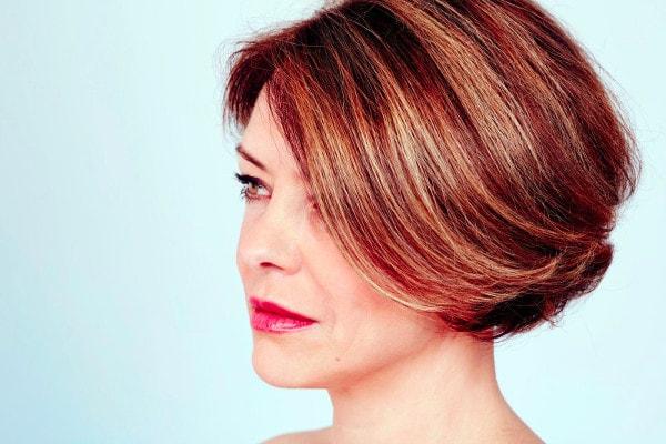 Une femme de profil avec une une coupe courte ornée d'un balayage
