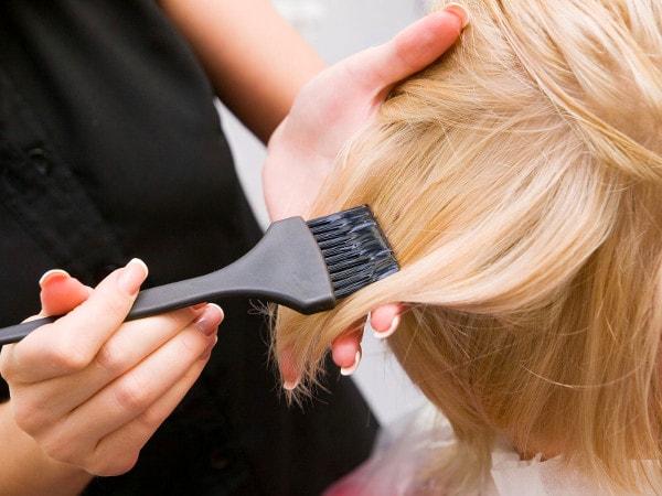 Balayage au pinceau sur une jeune femme à la chevelure blonde