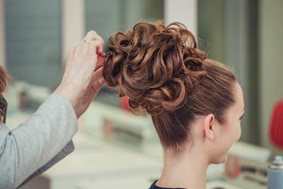 Une jeune femme assise coiffée d'un magnifique chignon haut orné de boucles anglaises
