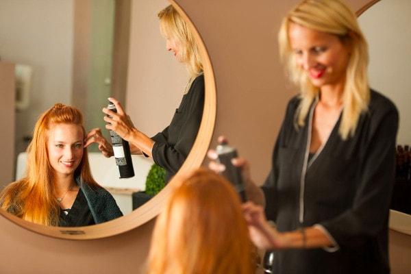 Une coiffeuse se tient debout à côté d'une cliente et lui applique de la laque sur les cheveux