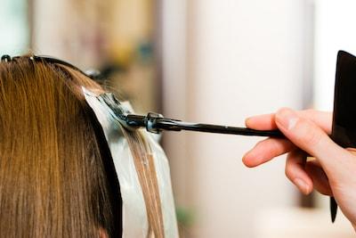Une femme avec du papier aluminium sur les cheveux qui se fait colorer les cheveux