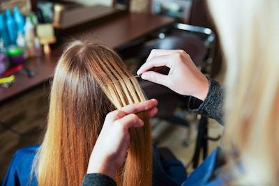 Une jeune femme à la chevelure châtain se fait colorer des mèches de cheveux en blond dans un salon de coiffure