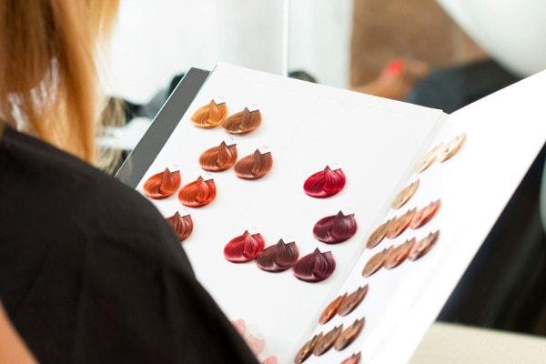 Une femme tient dans ses mains une palette d'échantillons de couleurs de mèches de cheveux