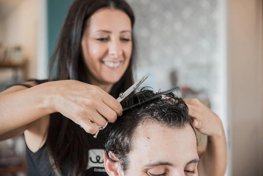 Une coiffeuse à domicile coupe les cheveux de son client