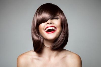 Une jolie femme avec une coupe carrée et une frange qui sourit la tête penchée vers l'arrière