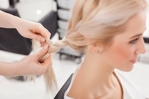 Une femme blonde aux cheveux longs de profil avec un coiffeur lui réalisant une tresse