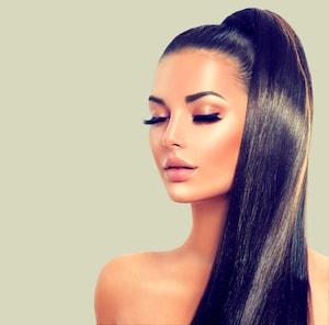 Une magnifique femme brune maquillée avec de longs cheveux attachés en queue de cheval version haute