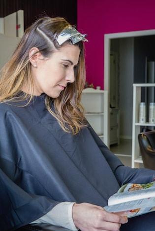 Une femme assise lisant un magazine en train de faire sa coloration tie and dye