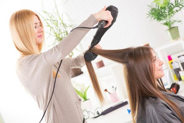 Une coiffeuse réalise un lissage à domicile avec brosse et sèche-cheveux