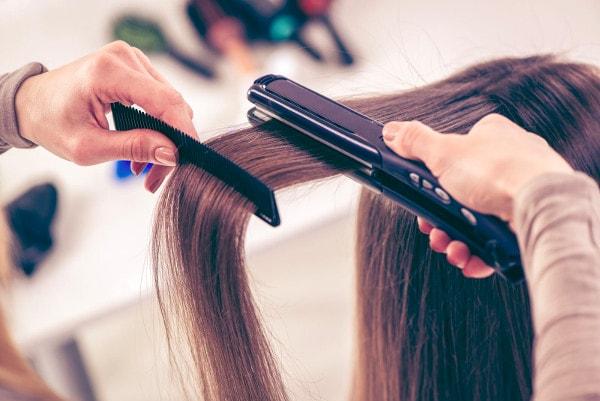 Lissage de la chevelure d'une jeune femme brune au peigne et au fer à lisser