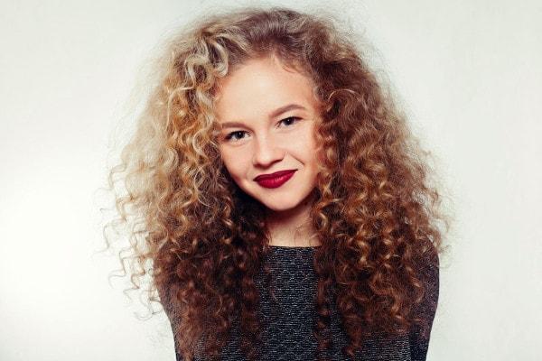 Une jeune fille souriante avec une permanente des cheveux