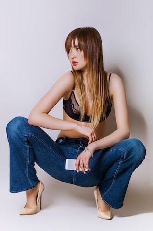Une jeune femme aux cheveux longs accroupie avec un tie and dye blond