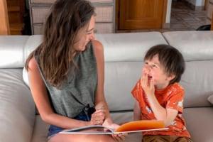 Une nounou lit un livre à un enfant qui rigole