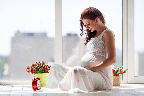 Une femme enceinte portant une robe blanche est assise en tailleur chez elle devant une fenêtre à côté de deux pots de fleurs et d'un réveil