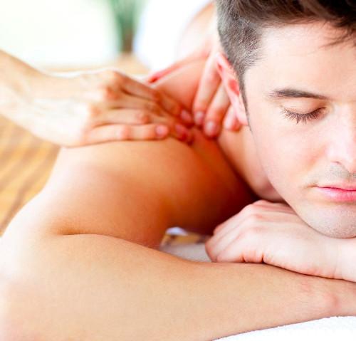 Un homme est allongé sur une table de massage et une masseuse lui masse les épaules