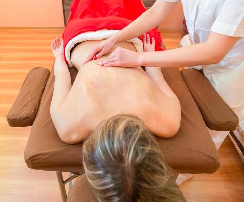 Une femme est allongée sur une table de massage et une masseuse lui masse le dos