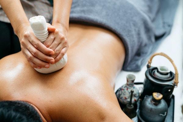 Un homme est allongé sur une table de massage, il est recouvert d'une serviette et une masseuse lui masse le dos en lui faisant un massage thaïlandais aux plantes
